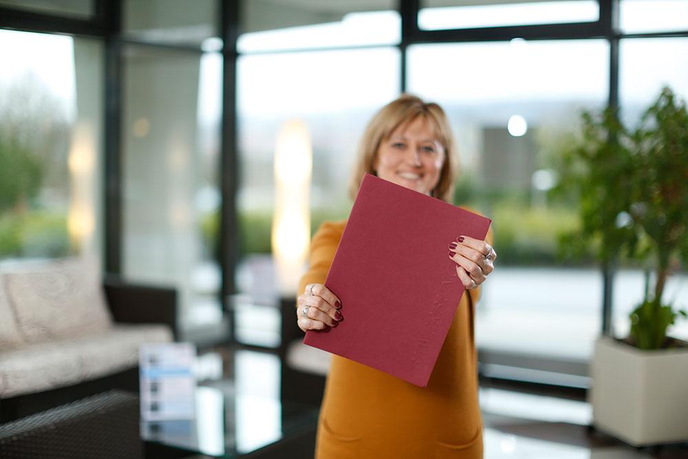 Karriere bei LICHTENAU e.V. - Frau hält Bewerbungsmappe in die Kamera